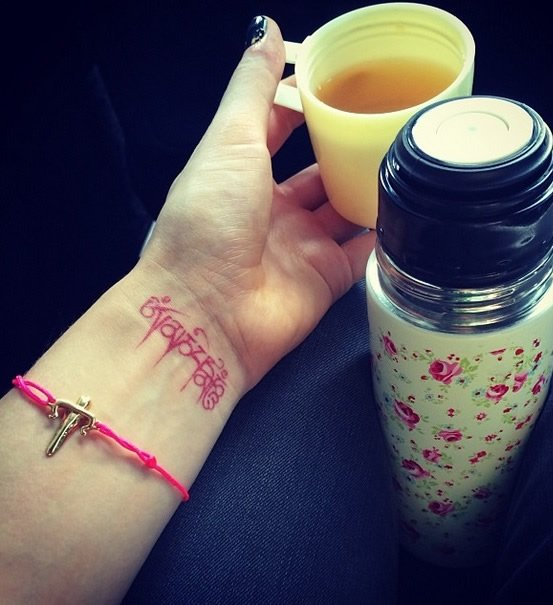 Ellie Goulding's Red Wrist Tattoo of a Tibetan Mantra